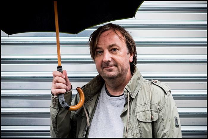 François Floret tenant un parapluie rafistolé devant un rideau métallique gris clair.